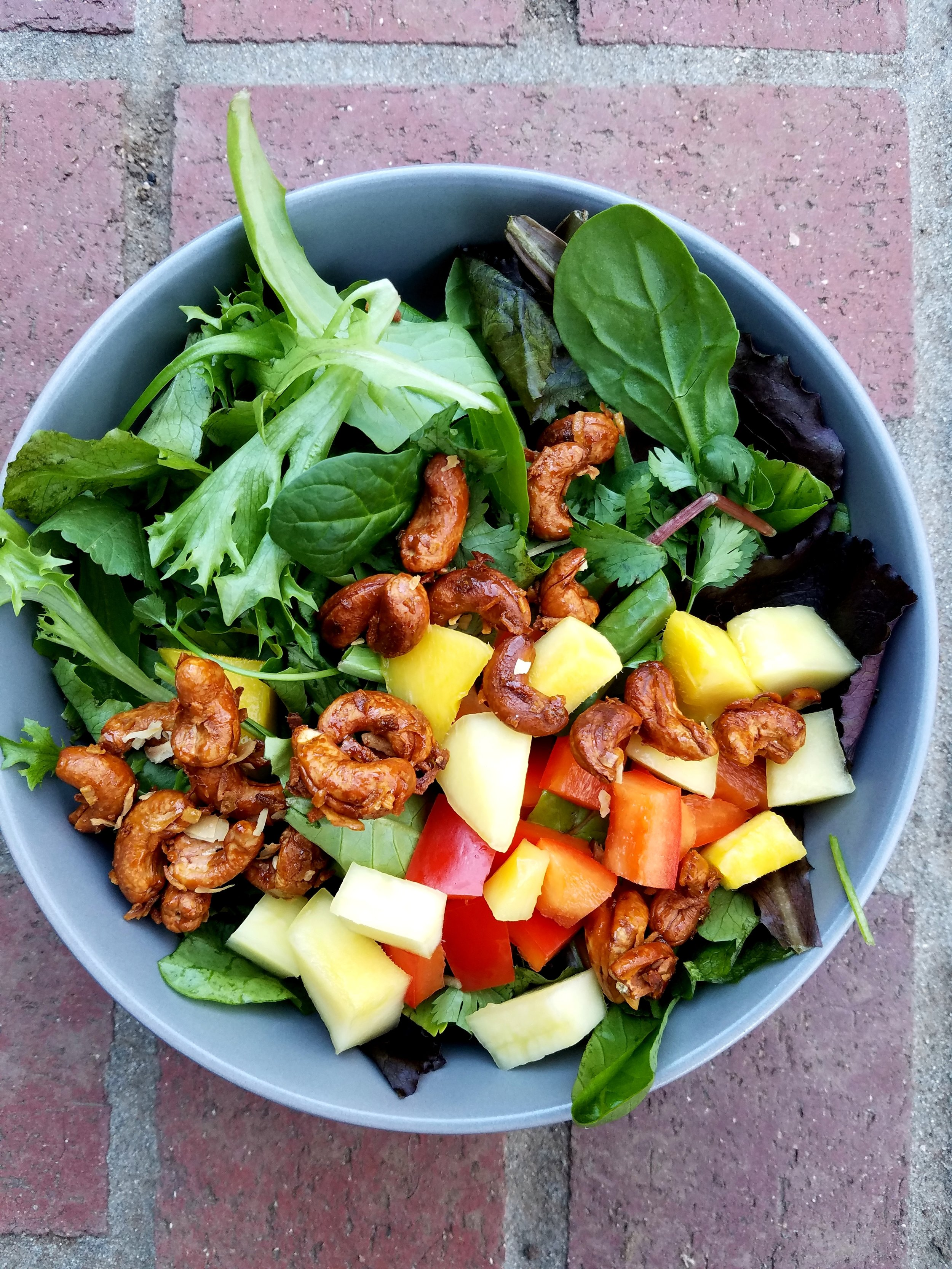 Fresh Greens topped with coconut cashews, mango, red peppers and apples