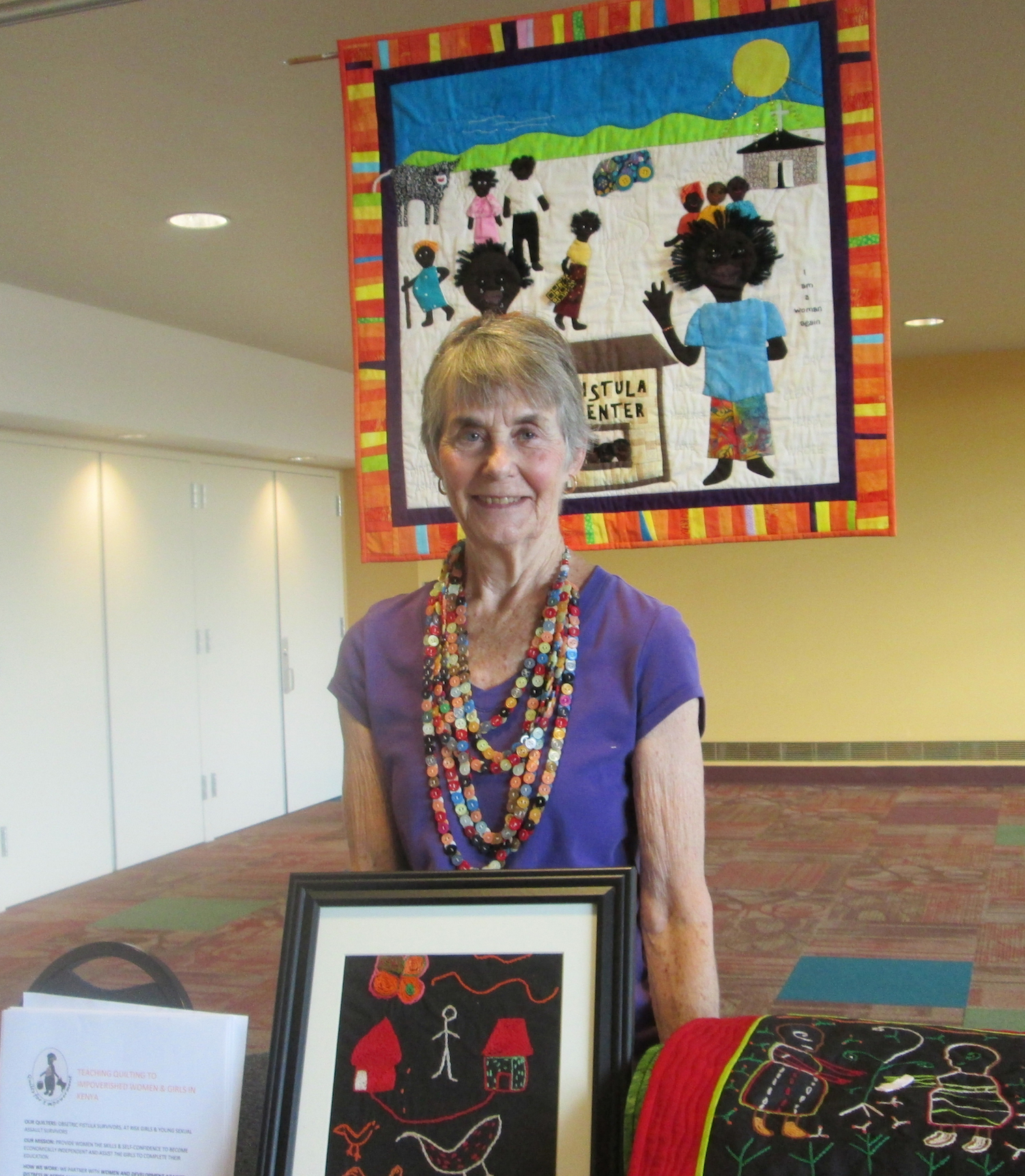 """Mary Ann McCammon at the NW Quilt Expo in September standing in front of her quilt titled: """"From tears to wholeness"""" that tells the story of a young fistula survivor's story."""