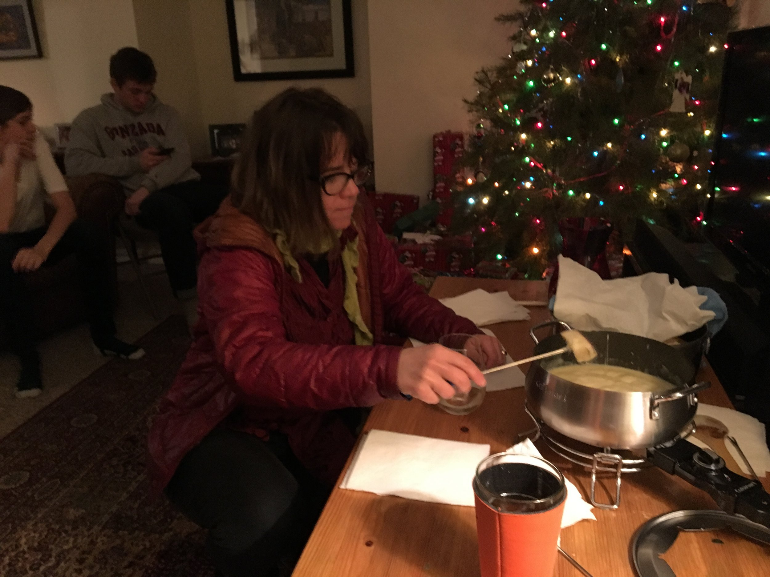 - Fondue is the tradition of Ron and Jan's family. That's Jenny dipping her piece of bread into the melted cheese.