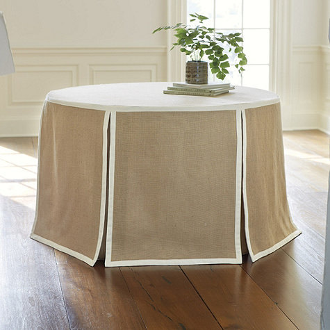 {Clean lines and classic colors let the accessories on this skirted round table shine. From  Ballard Designs .}