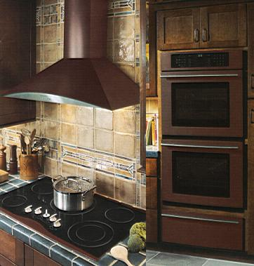 {Oiled bronze hood and double wall oven by Jenn Air, a fresh approach to appliance color.}