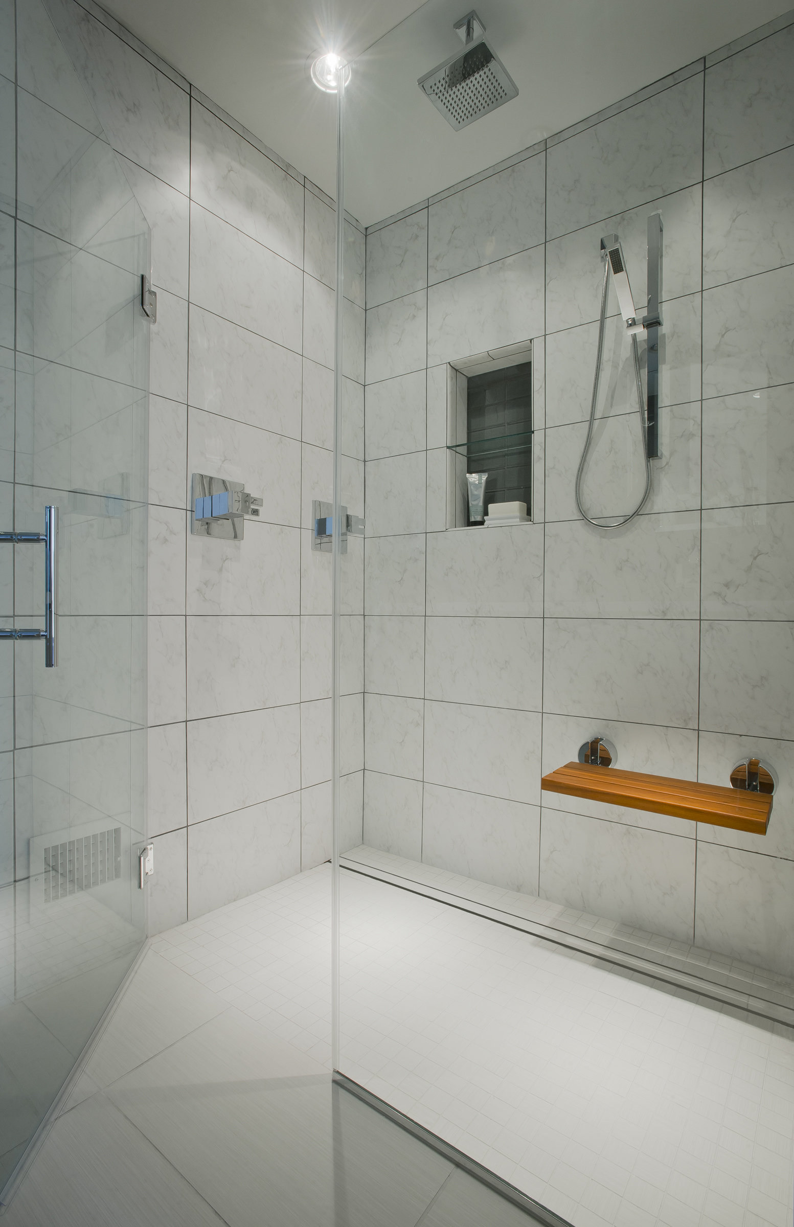 {New shower in award-winning master bathroom project. Curbless shower with glass doors, folding teak seat, rain shower head and wand all make for a great shower experience.}