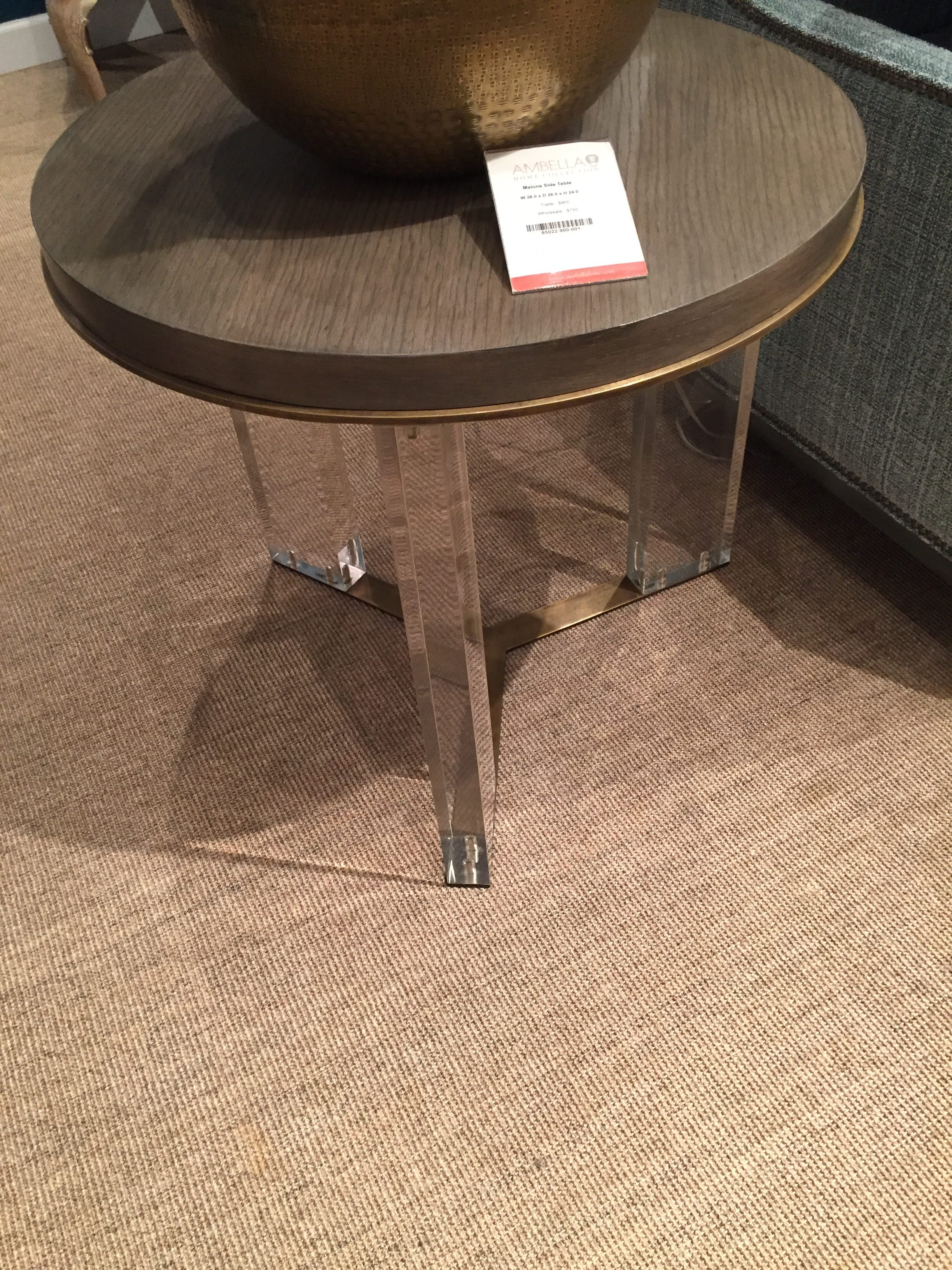 {Round side table with acrylic legs. From  Ambella Home .}