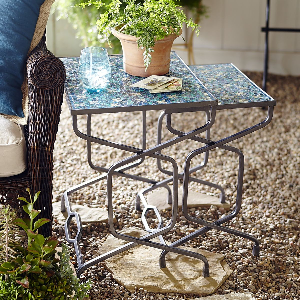 {The mosaic tile top of these nesting tables catch the sunlight, reminiscent of the ocean waves. From:  Pier 1 Imports .}