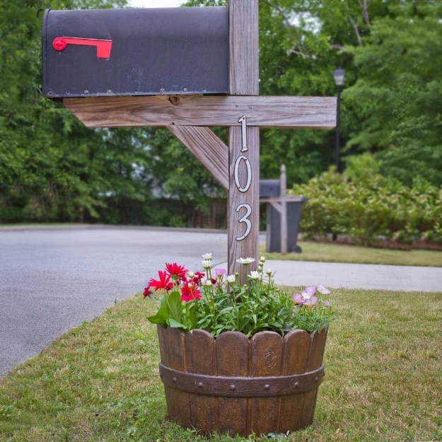 {Barrels planters are a familiar style, but this version gives the traditional piece a unique spin by framing the foot of your mailbox. From:  Home Depot. }