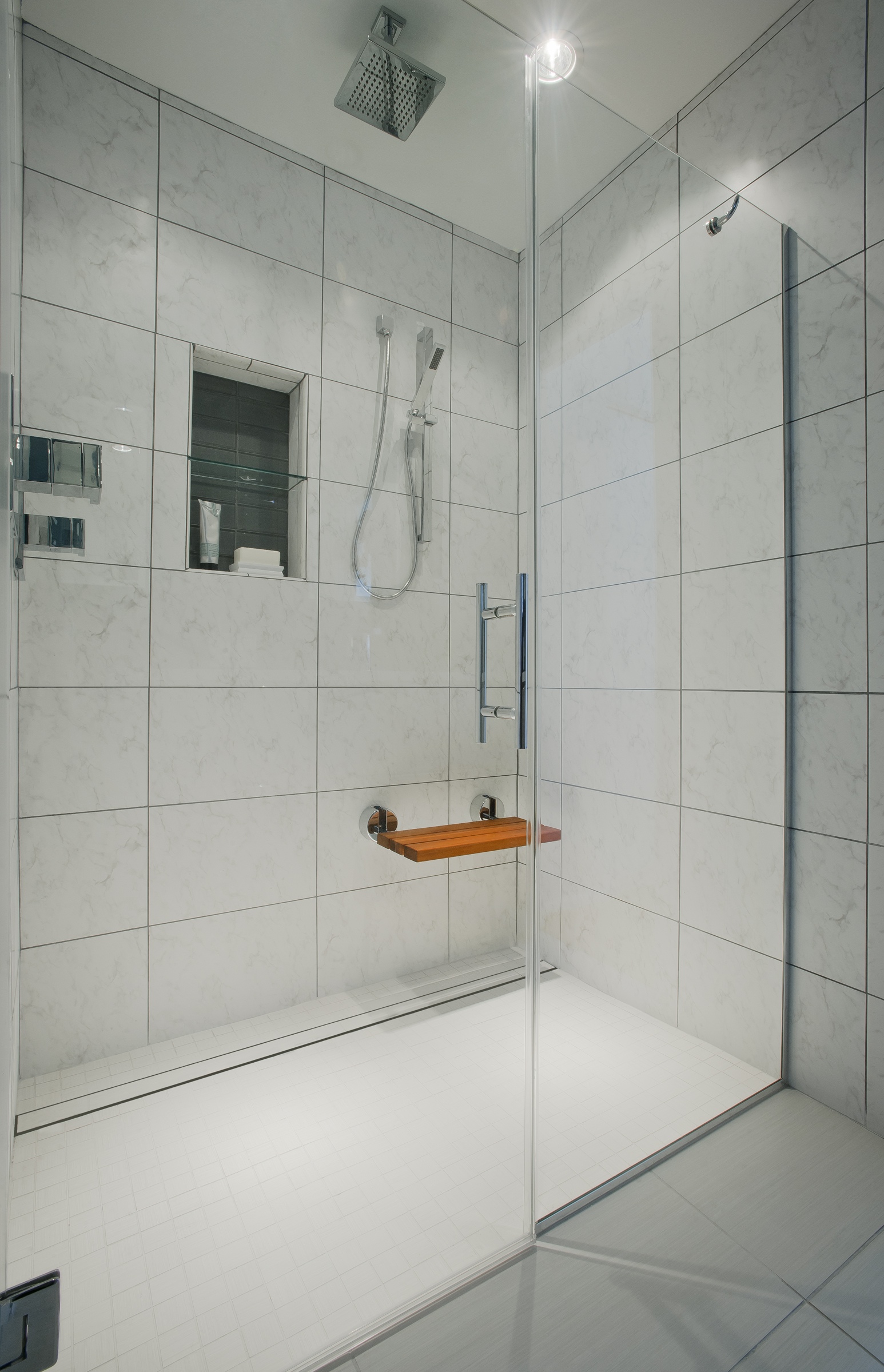 {A luxurious, walk-in shower with a railhead shower, shower wand and fold down teak shower seat. Designed by April Force Pardoe Interiors.}