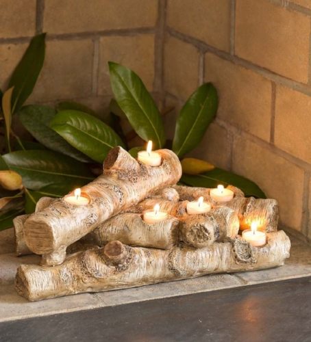 {Achieve a charming fireside glow in an unused fireplace with this sculpted faux birch tea light holder. From: Plow & Hearth,  available here .}