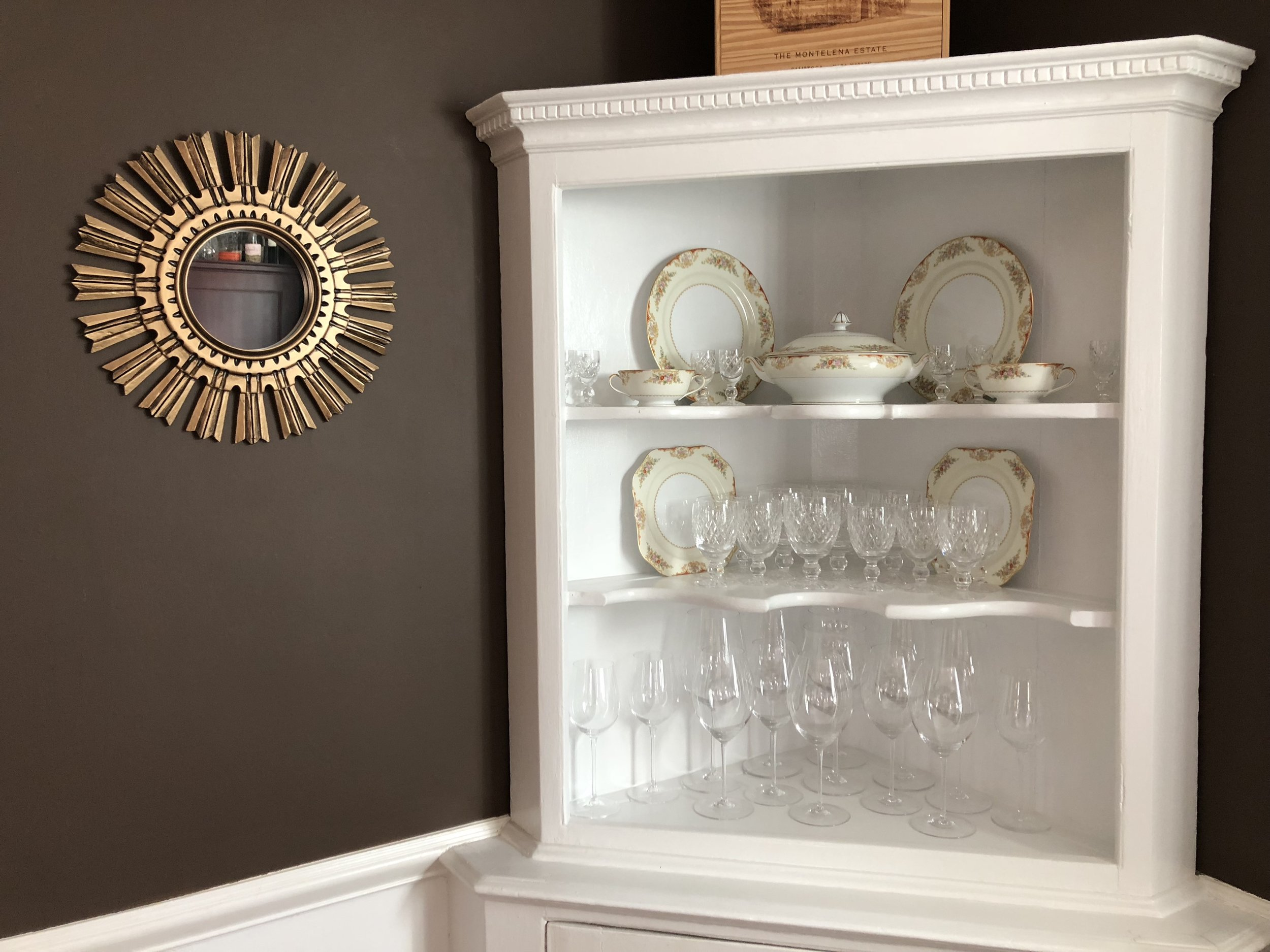 {Chocolate brown walls enhance the corner cabinet filled with family treasures to enhance any dinner party!}