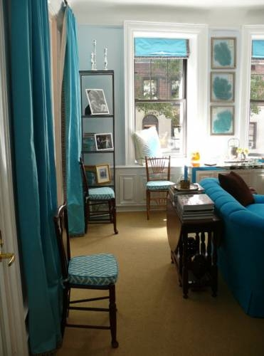 {Teal drapery panels and sofa, as well as other accessories, create a lovely & colorful room!}