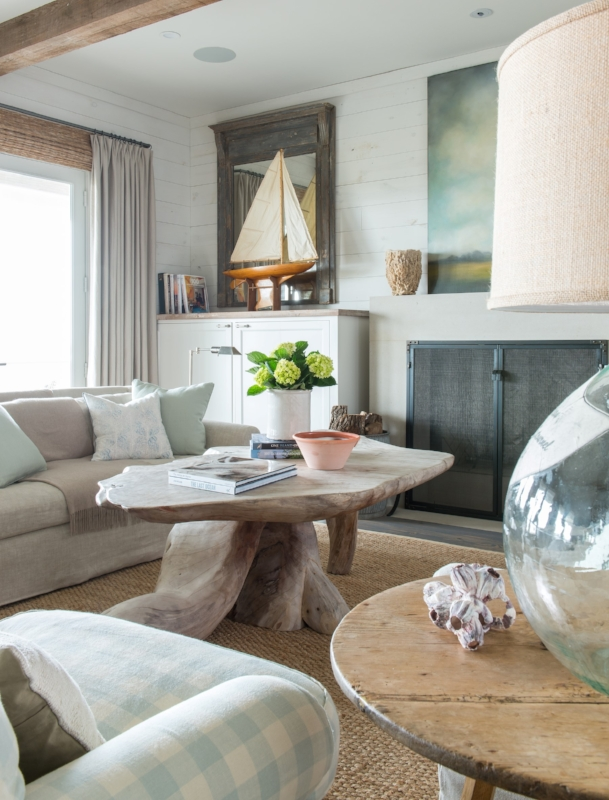 {The pale aqua blue throw pillows and upholstered chair are a happy greeting in this light and airy coastal-inspired room. Design by  Ginger Barber .}