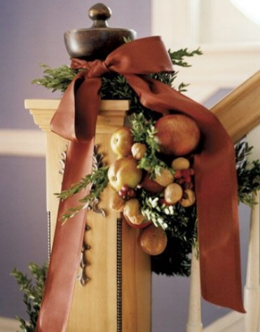 {The ribbon softens this lovely banister display, while adding a warm pop of color. From:  Country Living .}