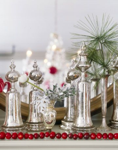 {Designer Kevin Reiner paired mercury glass with cranberries and evergreens for stunning mantle display. From:  Country Living .}