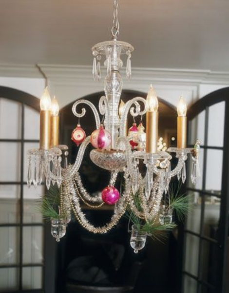 {Designer Kevin Reiner jazzed up this crystal chandelier for the holiday season with garland and ornaments. From:  Country Living .}