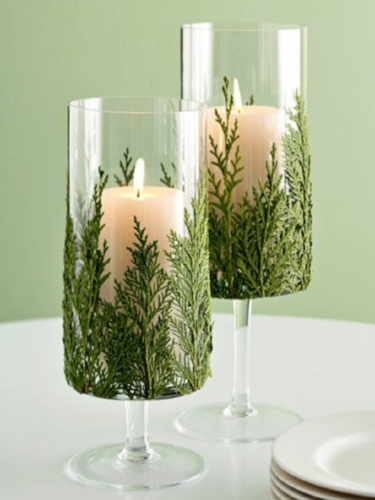 {For a seasonal DIY project, glue fresh evergreen stems to the outside of clear glass candle holders! From:  TrenDecor .}