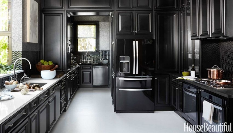 {This spacious kitchen achieves its sleek look with black cabinets and appliances. From:  House Beautiful .}