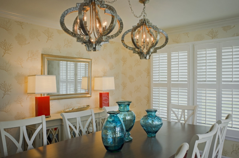 {The quatrefoil chandeliers provide ambient light for dining, while the coral table lamps on the sideboard offer a layer of decorative lighting. Design by  April Force Pardoe Interiors .}