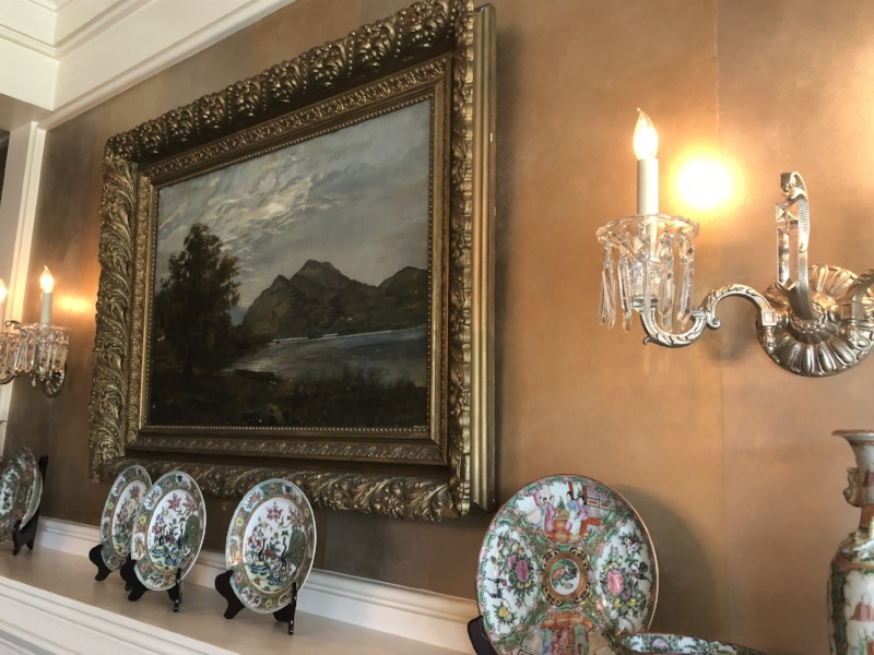 {Family treasures fill the Marriner dining room, including this landscape painting by Randy's great grandmother and his family's handed-down china collection.}