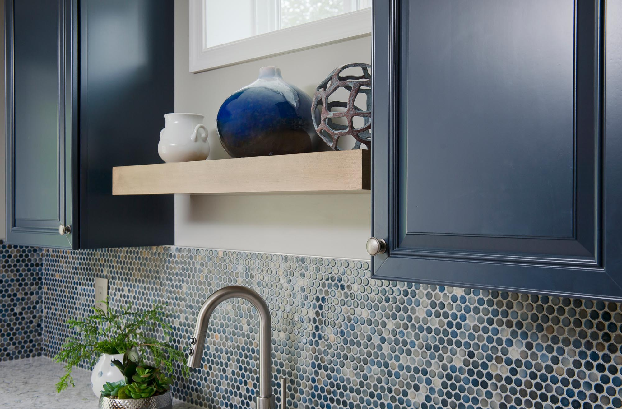 Sink with blue tiled backsplash and small potted plants