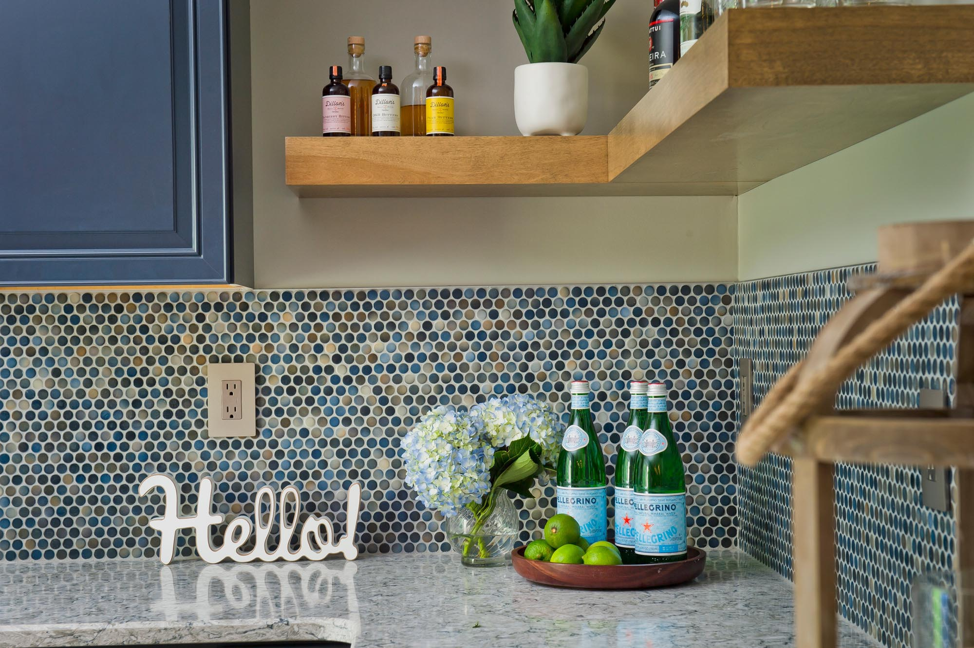 Marble counter top with blue tiled backsplash and mini bar