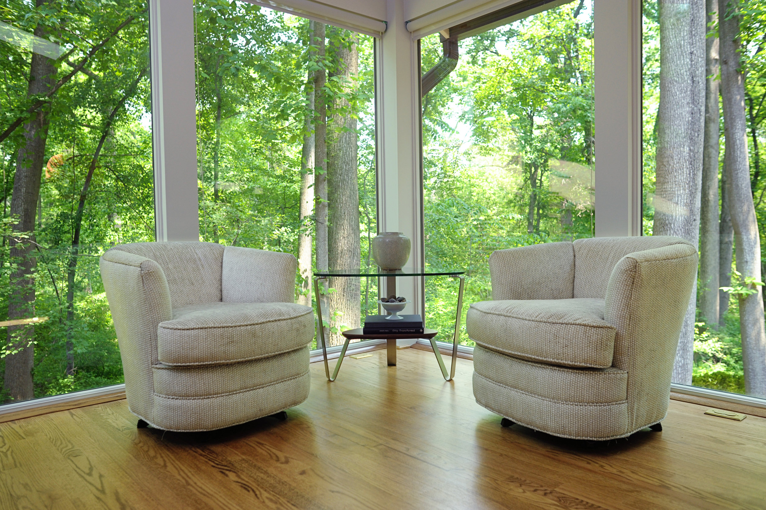 {A pair of swivel chairs is perfect for a cozy conversation (or taking in the amazing view outside!).  Blue Sea Drive  design by April Force Pardoe Interiors.}
