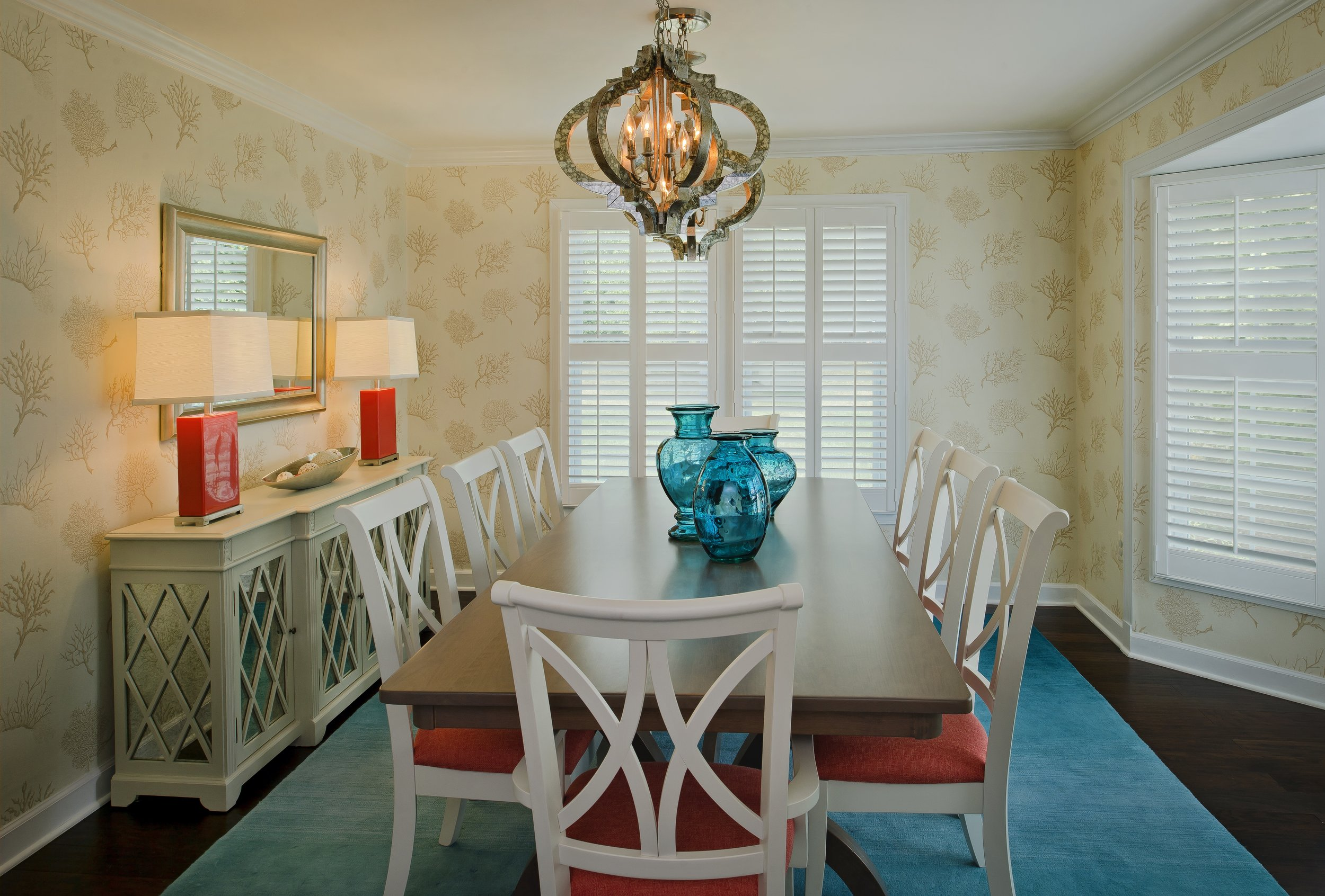 {To light this rectangle-shaped dining table we used two round chandeliers instead of one long one. We also added two lamps to the buffet, providing another level of light to the space.  Saddle Ridge Terrace  design by April Force Pardoe Interiors.}