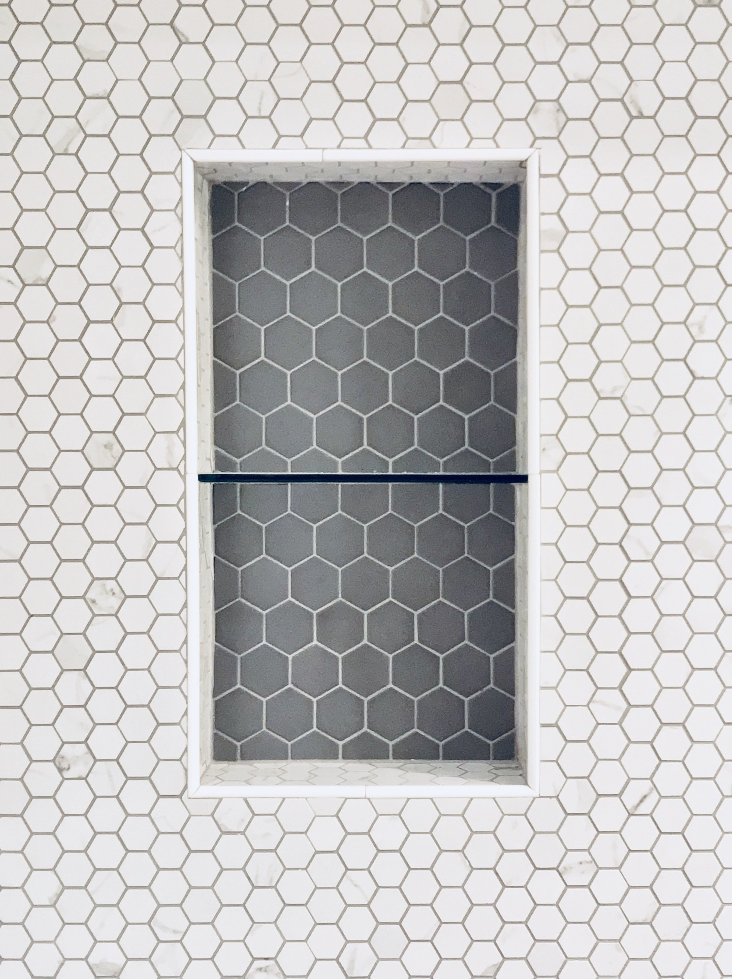 Shower niche with white and gray hexagon tiles