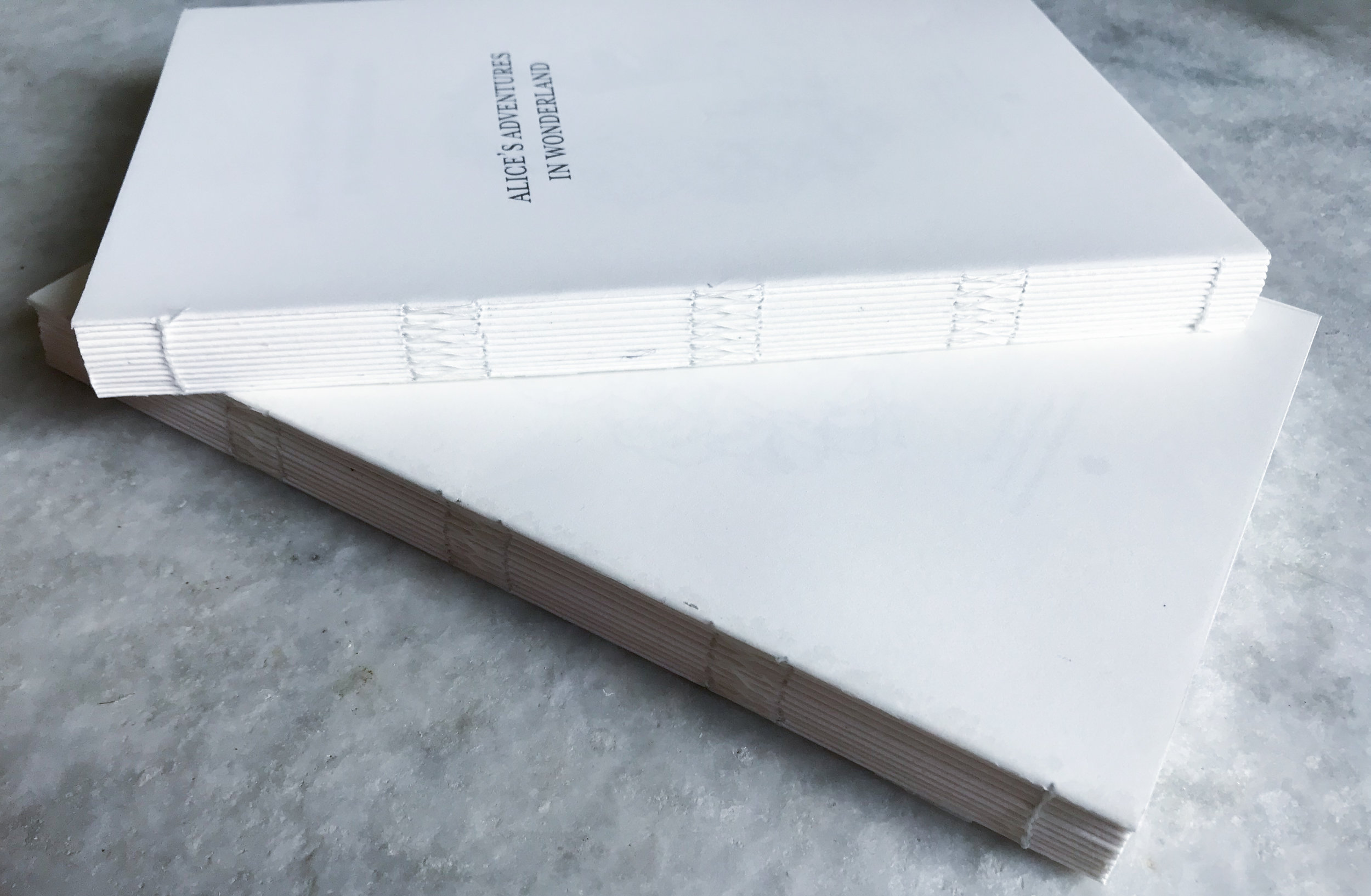 Glued spine with stitching