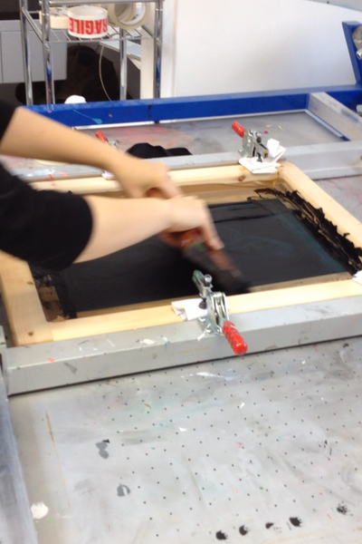 Using a squeegee when screen-printing to push the ink through the stencil