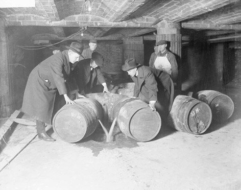 Prohibition agents emptying barrels of whiskey