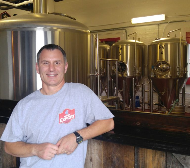Jessy Jolicoeur, owner and brewer of Oval Craft Brewing, in front of his 10 bbl brewhouse inside the former military base fire station