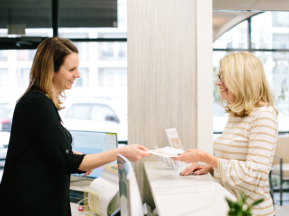 Receptionist talking with happy customer