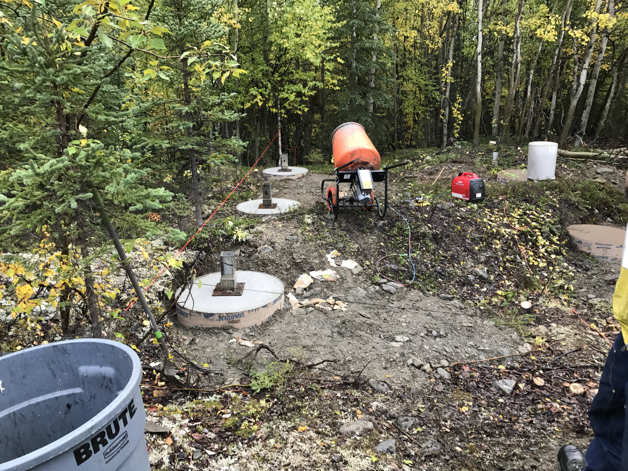 Water was transferred from the cold rushing Tiekel River less than a mile away, to blue jugs then garbage cans, to mix the 900lb.+ footings.