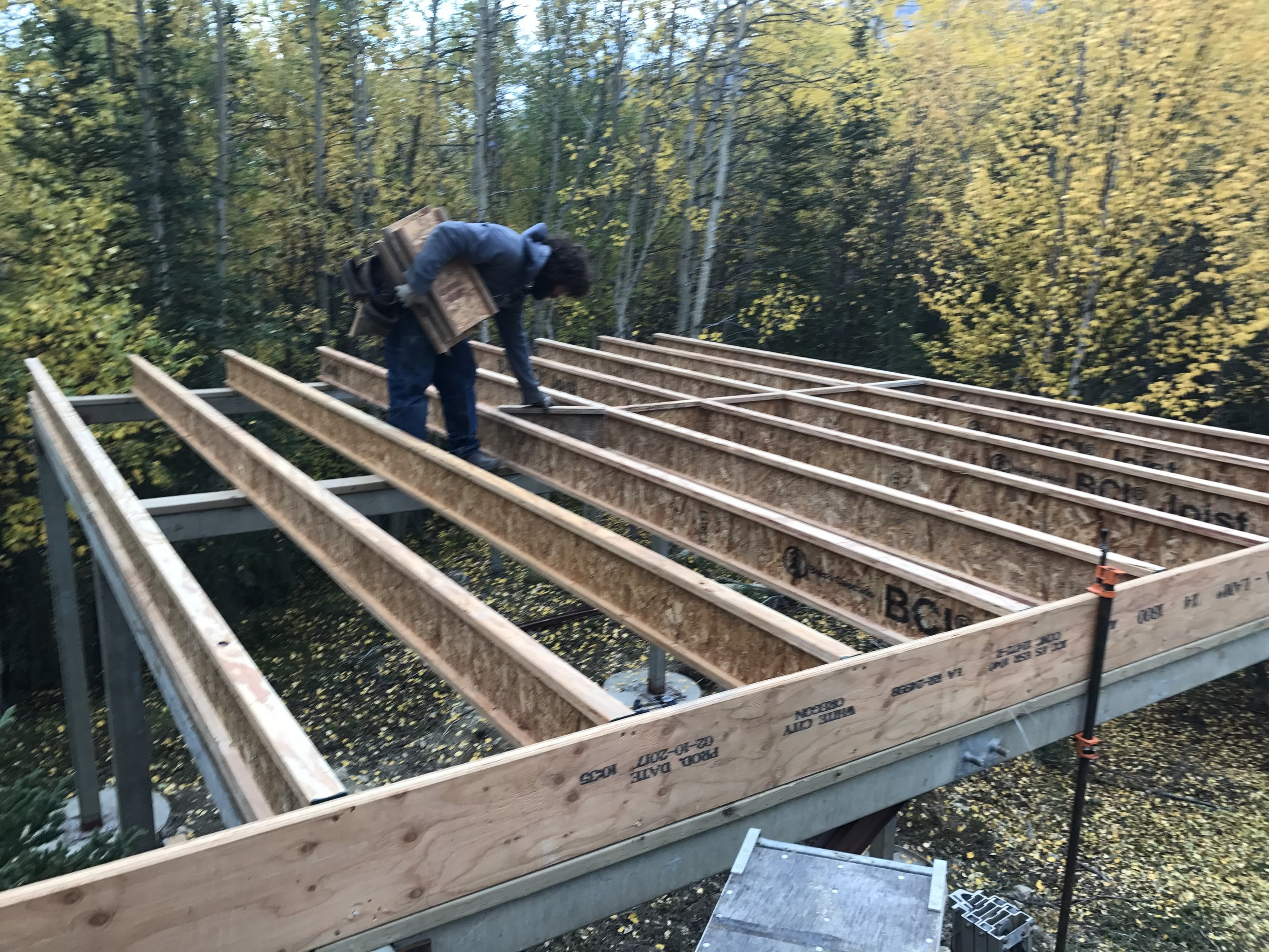 """Pressure treated 2x6s were attached to the elevated metal frame and BCIs were attached to laminated lap boards to make the frame. 1 1/8"""" tongue and groove decking was glued and nailed down to form a solid deck and base for the timber frame."""