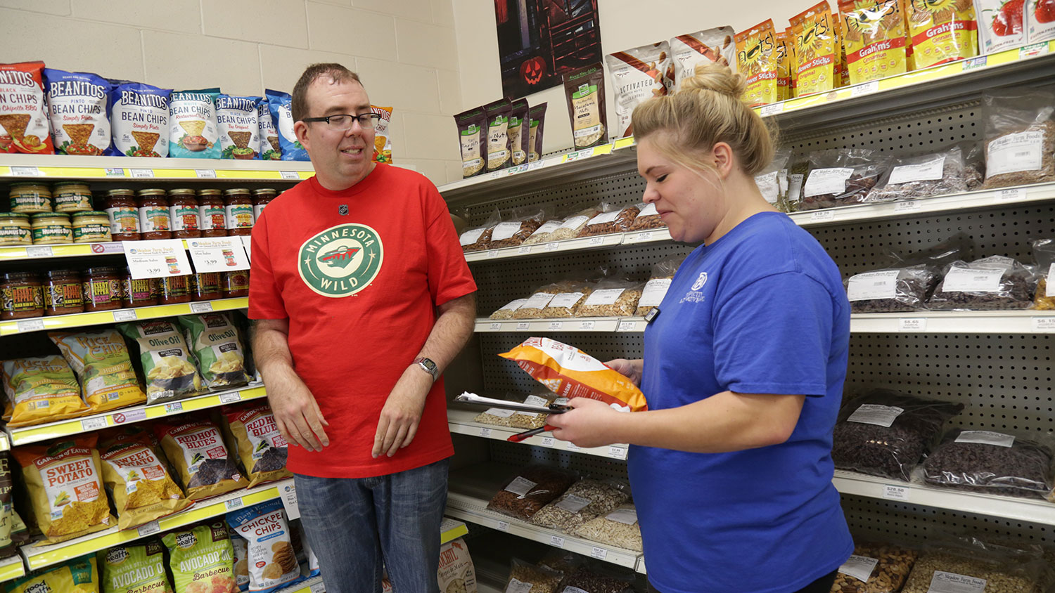 A job coach works with a PA client stocking groceries.