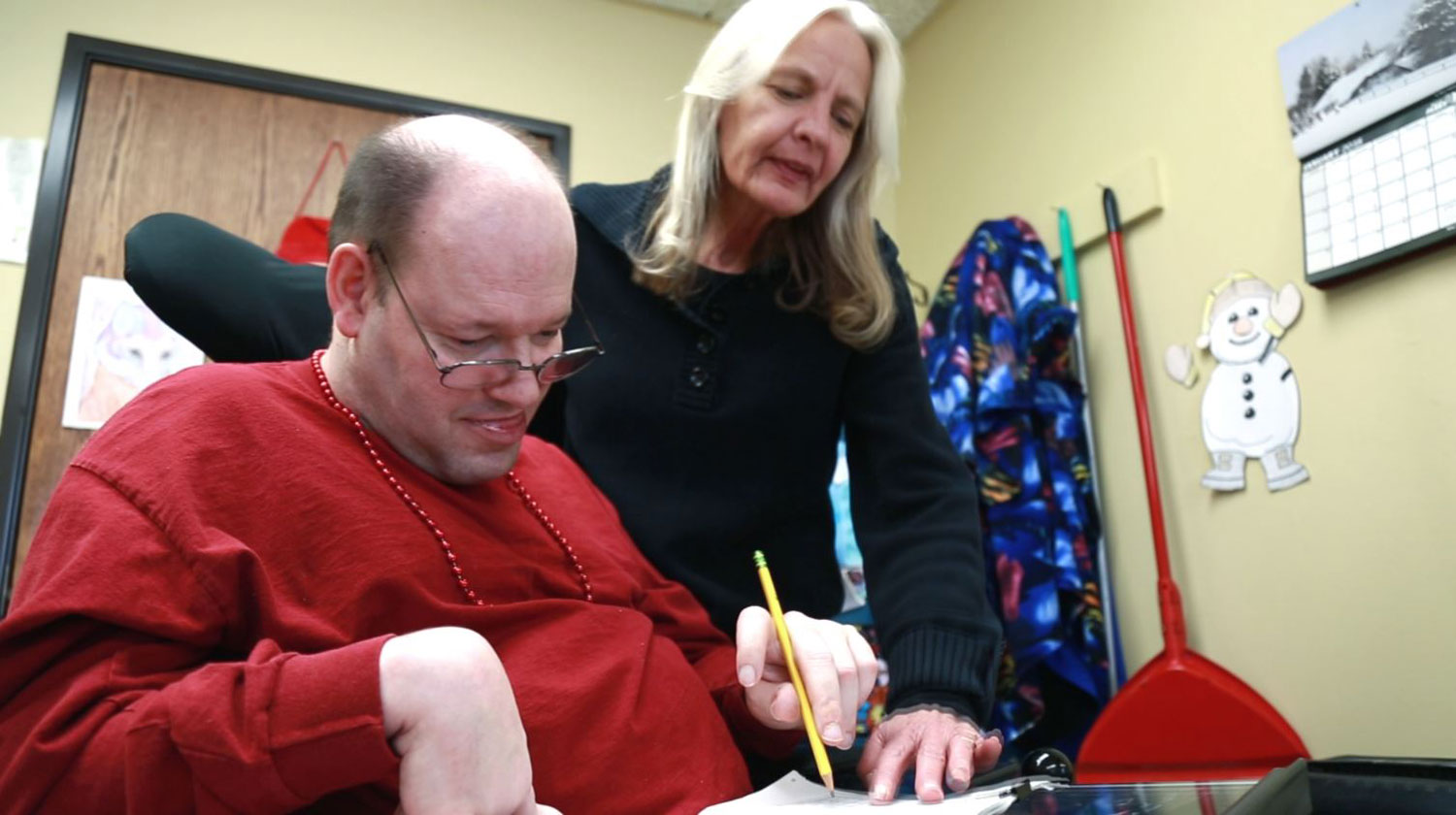 A volunteer holds paper while a PA client writes.