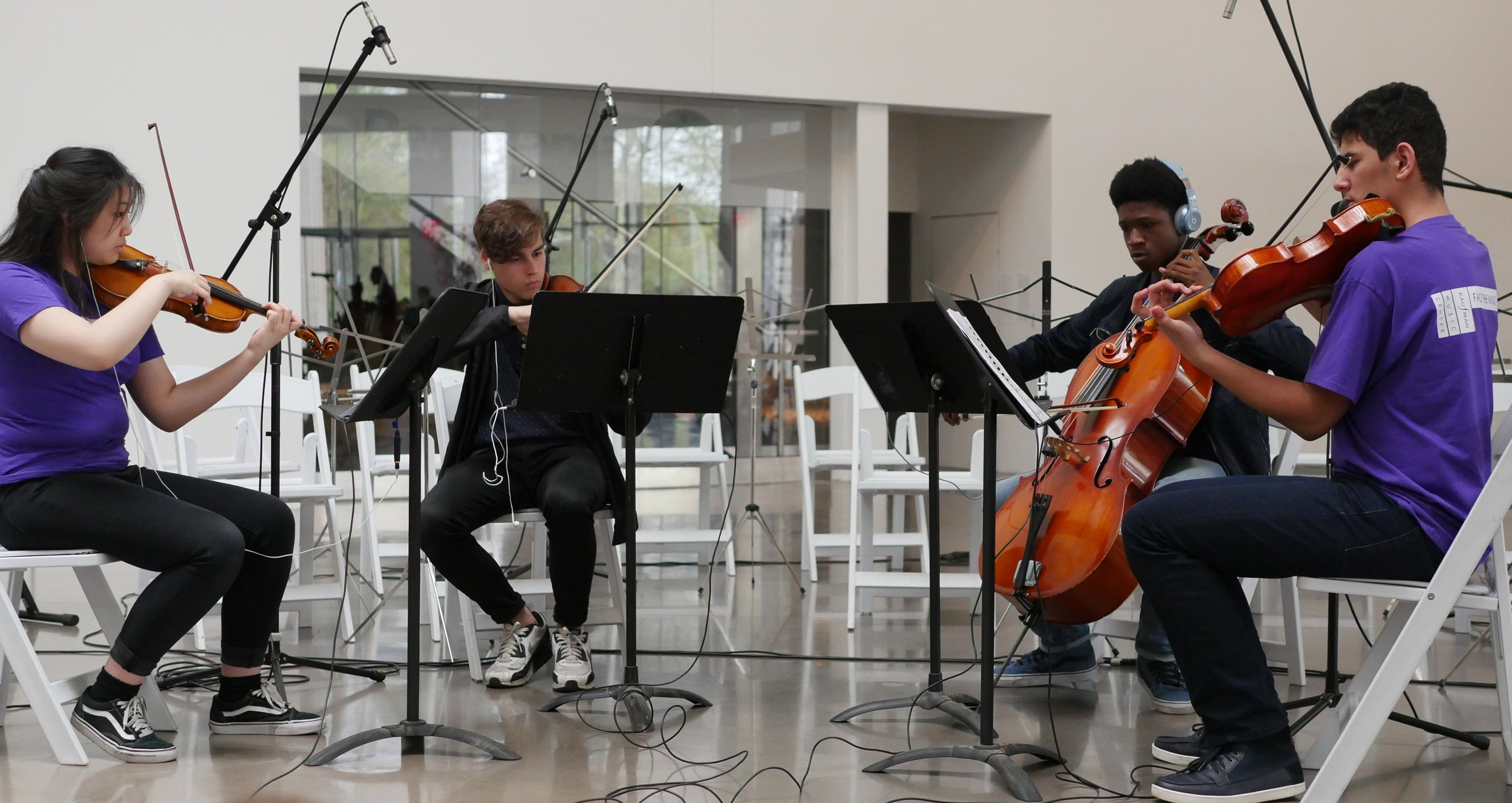 """Members of the Kaufman Music Center's Face the Music ensemble perform """"Stage III (Grace)"""" from  Recurrent Stages  at the Queens Museum, Queens, NY Colleen Bixler and Ruby Pine, violins; Amirah Stewart, viola; Layla Krantz, cello"""