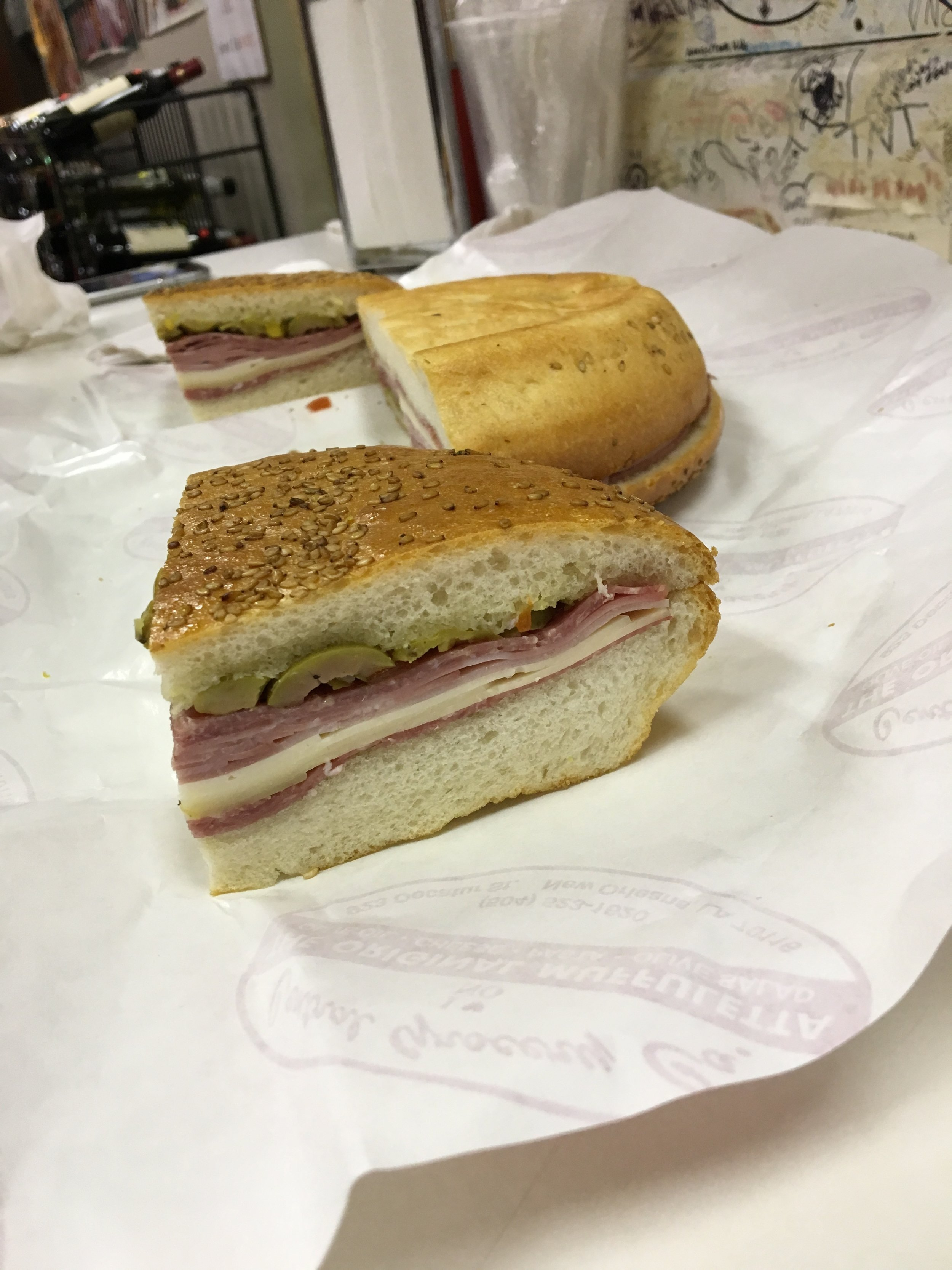 """Full 10"""" Round Muffuletta - they cut into quarter portions. Love how the sesame bread soaks up the olive oil and briny/marinated goodness."""
