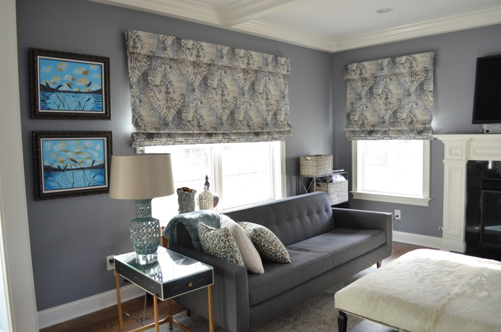 Gray painted wall living room design with patterned curtain and  paintings on the wall