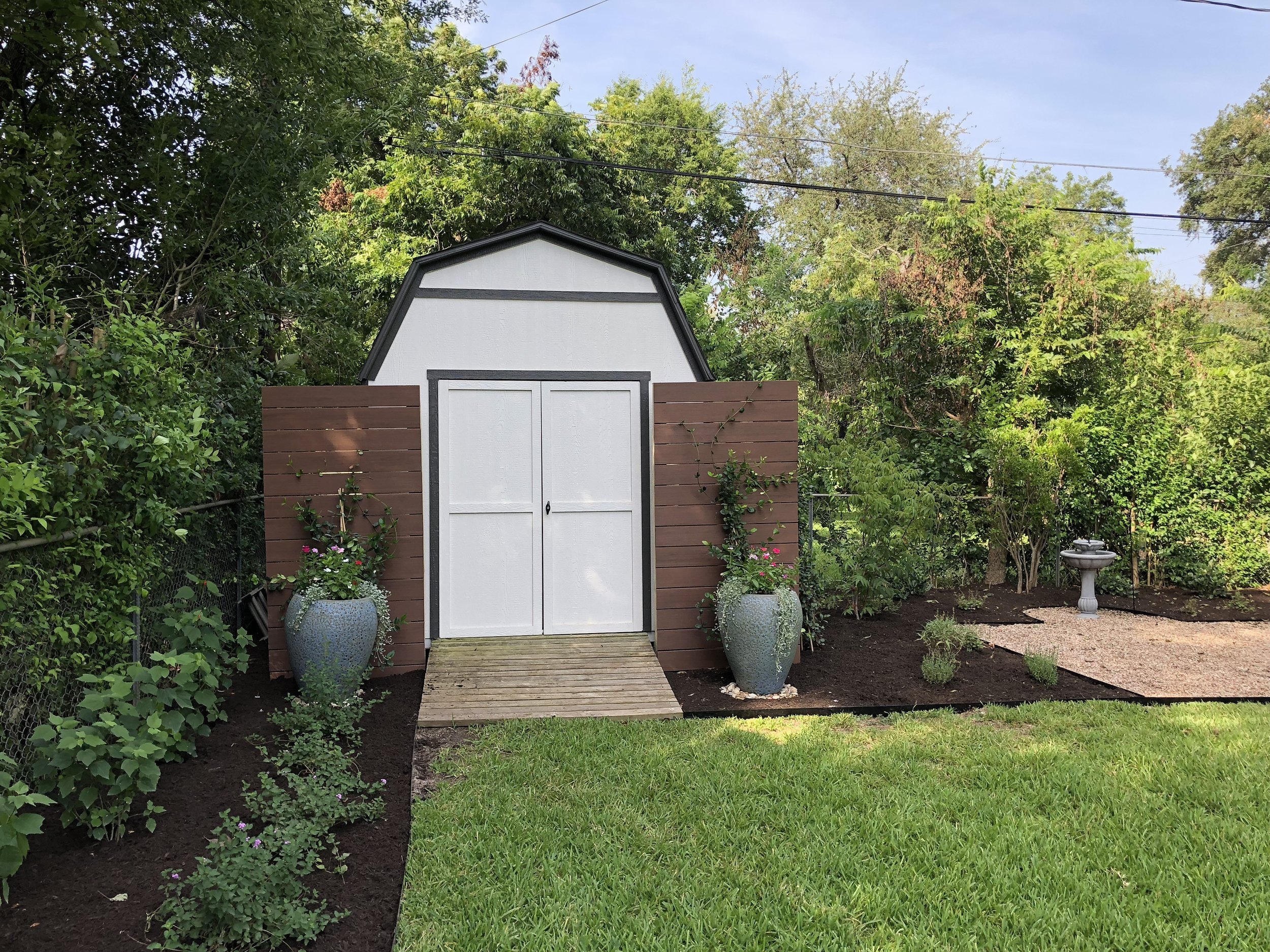 The existing shed was dressed up with a screen, vines, and flower pots.