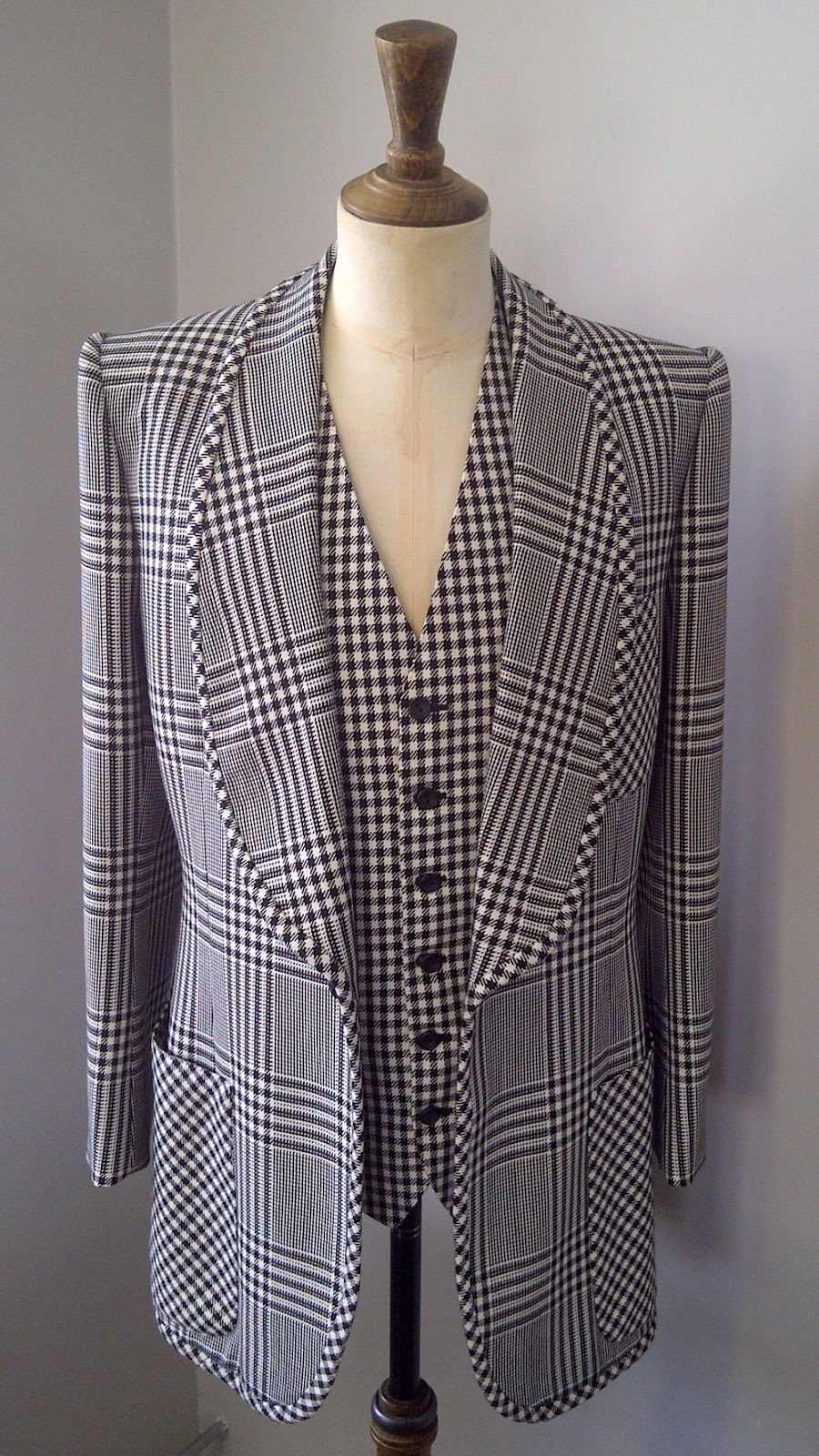 This is a Tommy Nutter suit too,and its clearly a Glen check (Prince of Wales) and a houndstooth (that looks like a gingham) combo. Not actually exactly what after, but same look. Graphic, monochrome check. Roger? Check. -