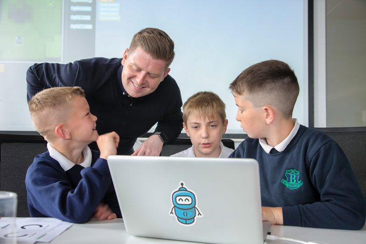 Code Club volunteer, Gavin Friel, helping out Blythefield pupils during their visit to Neueda