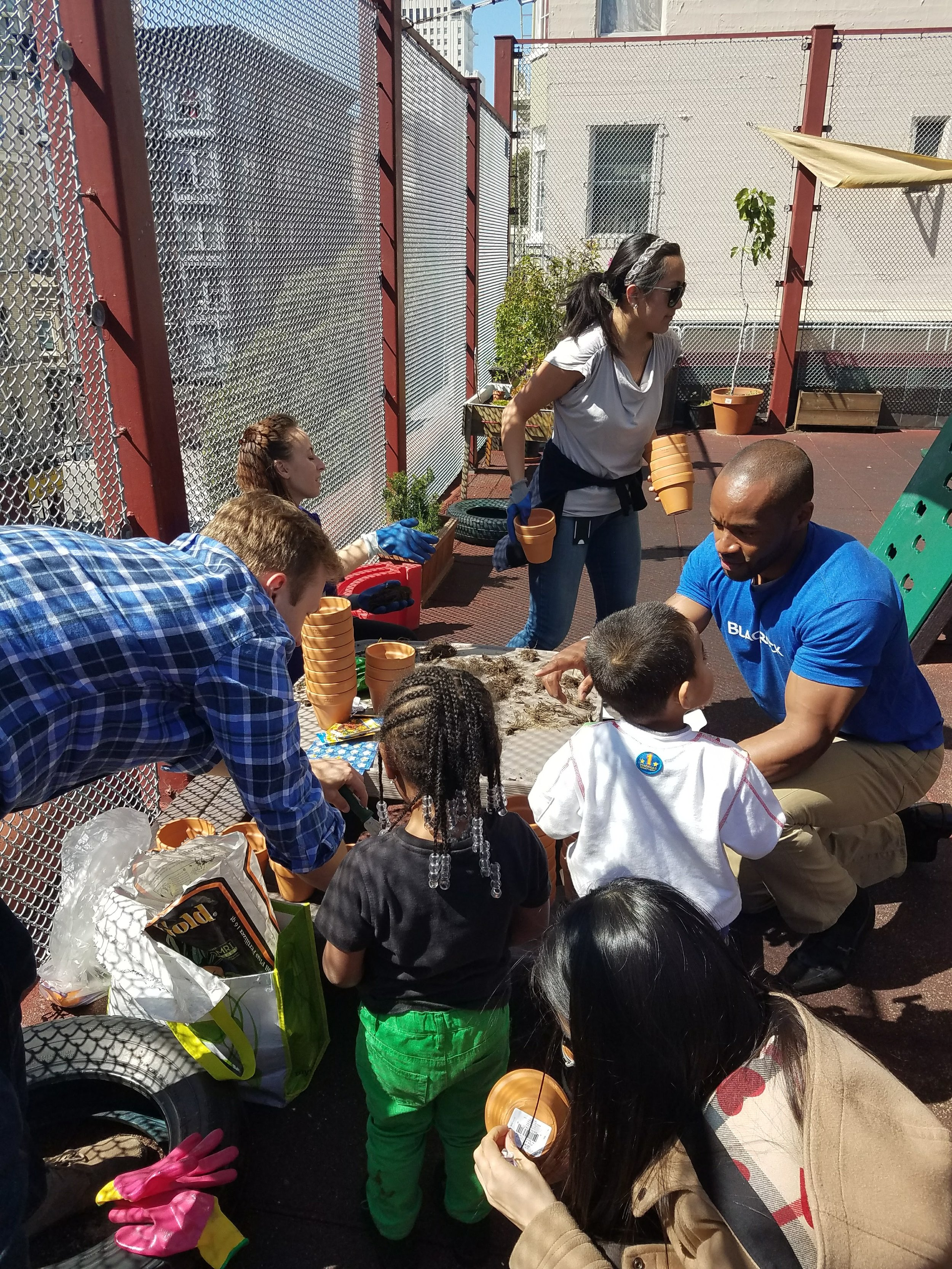 BlackRock employees helping our students at Compass Children's Center learn gardening.