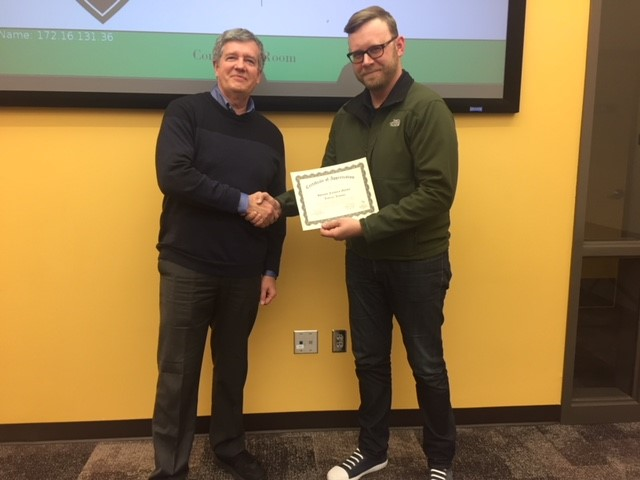 Sprouts Lenexa Store Manager Jaysen Pauley receives a Certificate of Appreciation from Foundation President Doug Allen at the January 31st Foundation Board Meeting