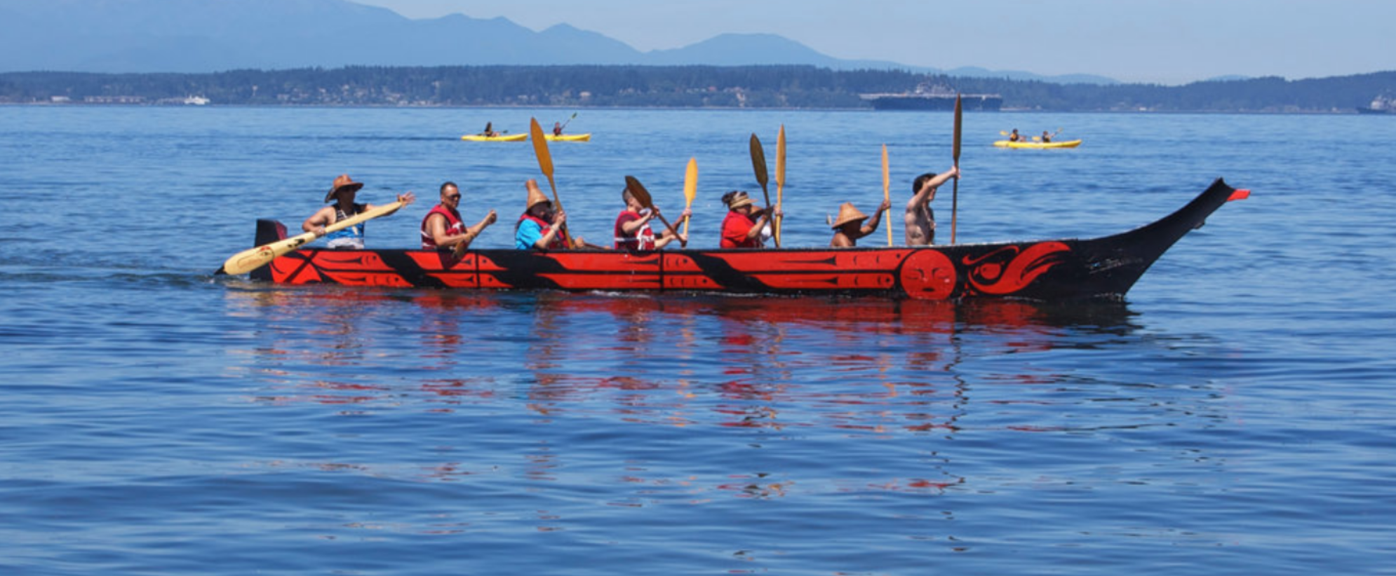 Duwamish tribal members paddle aboard a tribal canoe called The Raven.