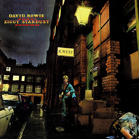 This album was released on 16 June 1972. It was photography by Brian Ward. Who has photograph David Bowie multiple time during his career. Some people say it was because of this image and David Bowie poetry of the character of Ziggy Stardust that catapulted them to fame.   What strikes me first is the use of colour in this image. Straight away the colours stand out, drawing the audience into the image. The use of the warm yellow lighting, lights up the streets as well as David Bowie in a blueish greenish clothing and his purple boots. I admire how much detail the photographer has put into this image. With each corner having something to express, whether it's the depressing weather or the flickering lights in the windows.