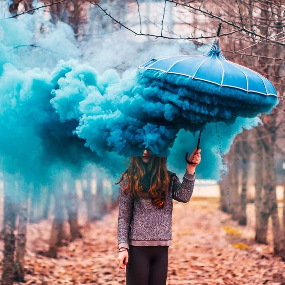 this image is one that caught my eye, although unusual it made me explore how i could capture the same result using the smoke bomb in place of the head.  I like how the background is soft and out of focus in the contrast with the dominating strong vibrate blue  smoke bomb giving off the layers of bright blue, like clouds under the cover of the umbrella. It fills nearly 50% of the image but the eye is drawn following the pillows of smoke bomb across the top of the photo.