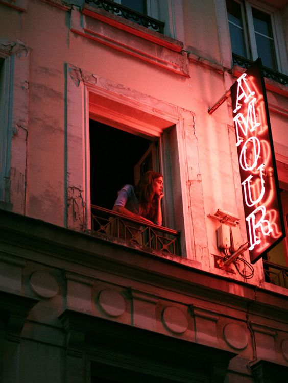 "I find the red neon signage reflecting on the woman's face and body, against the grey contrast of the building giving off a ""Romeo & Juliet"" type scenario in a European city. Although the colour palette is quite minimal it works really well, your eyes follow the light and then across to the woman wondering what she is thinking .... is she waiting for someone ? is she just taking time out to absorb what is happening below ?"