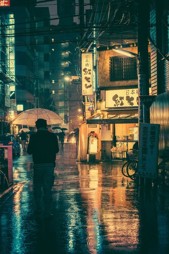 This busy wet, glistening pools of  rain water in the street scene focusing the eye on the main  umbrella with the light matching that of the shop to the right which has several of the umbrellas outside. The tall dark buildings central to the photo above, with more of  the umbrella theme ahead with all the rushing of people  to get to their destination