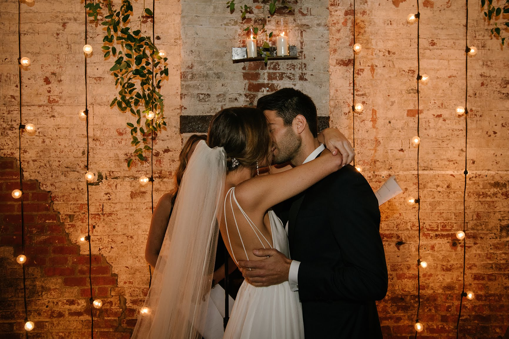 Kristi & David would describe their wedding aesthetic as industrial minimalist - they embraced the 'less is more' mindset. The Green Building is a raw, industrial warehouse with exposed brick walls and high, open ceilings. The couple incorporated string lighting, suspended greenery, and copper accents. The reception also had a non-traditional approach, with lounge seating that encouraged guests to move around the room, mingle, & dance. The night was capped off with churros (instead of wedding cake) and an empanada food truck for late-night eats.