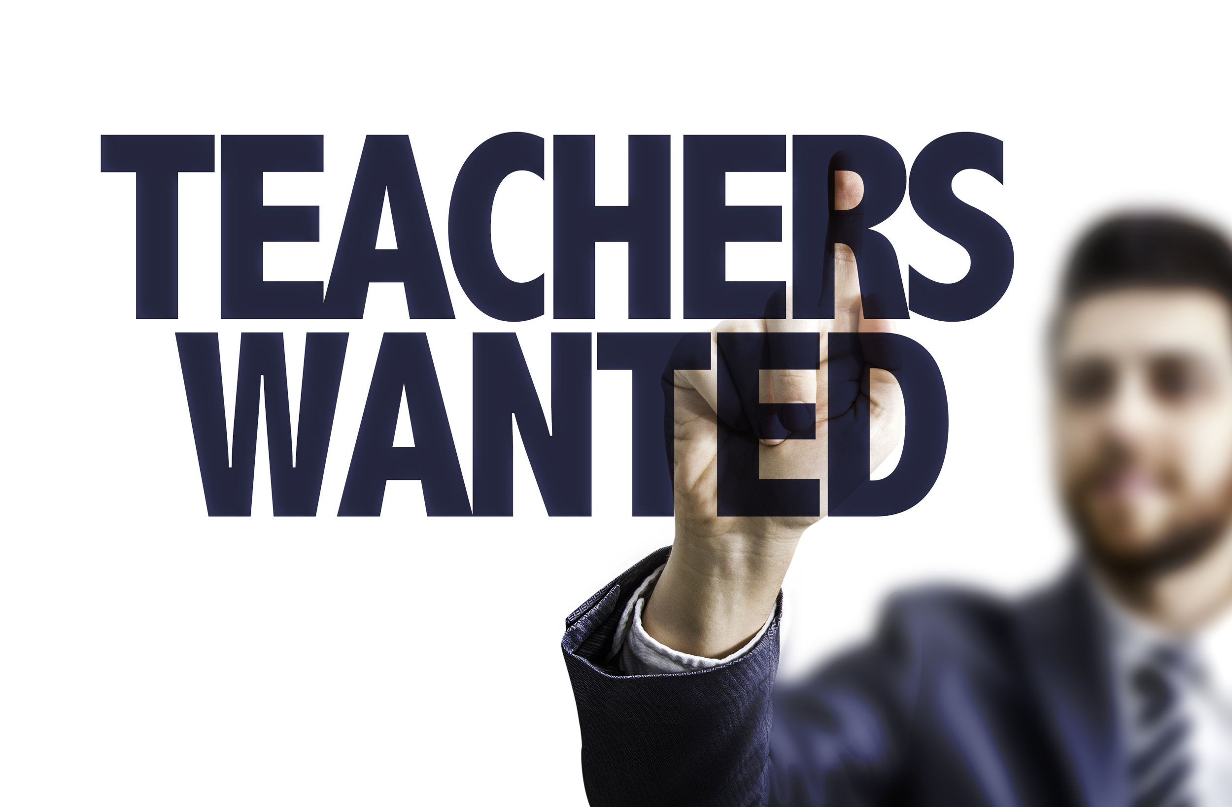 Business man pointing the text: Teachers Wanted